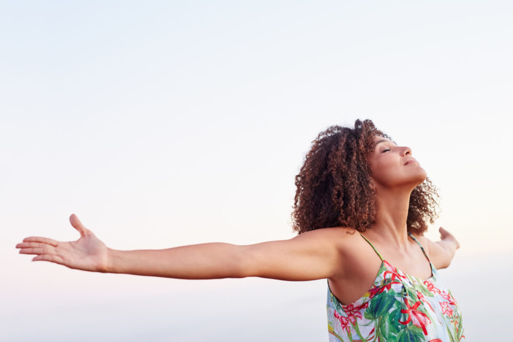 Woman outdoors with her arms outstretched and her eyes closed expressing serene freedom